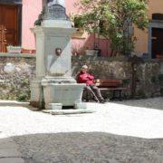 Burgund-Mann schlaeft am Brunnen